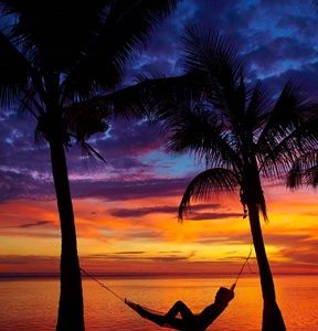 Woman in hammock, and palm trees at sunset, Coral Coast, Viti Levu, Fiji
