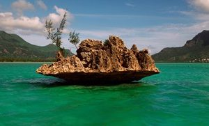Rock in Indian Ocean with mountain the background, Le Morne Mountain, Mauritius Island, Mauritius
